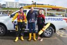 RNLI volunteer crew Charlie Green, Community fundraising Manager James Clarke and lifeguard Ellie Woodward launching Mayday